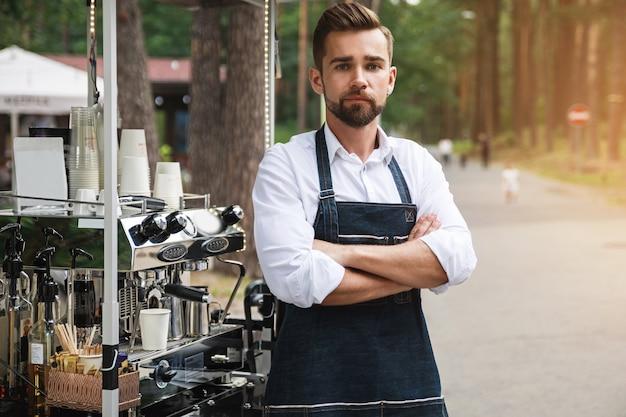 그의 움직일 수있는 거리 커피 숍에서 일하는 동안 잘 생긴 바리 스타 남자