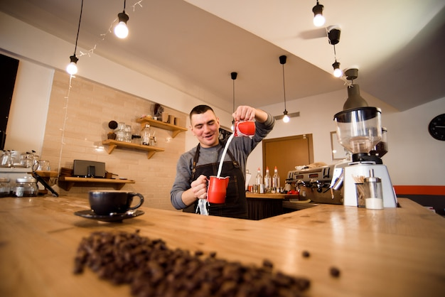 Handsome barista preparing cup of coffee for customer in coffee shop.