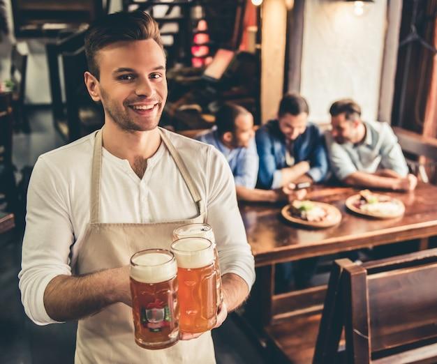 Handsome bartender in apron is holding beer.