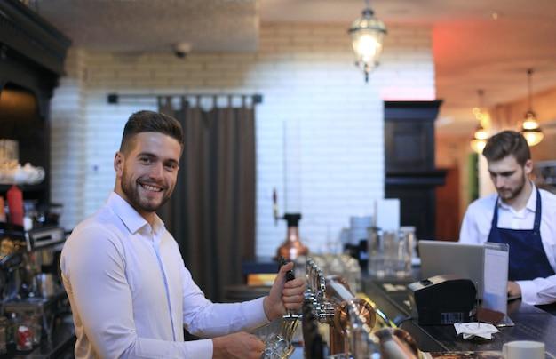 잘생긴 바텐더는 술집의 바 카운터에 서서 미소를 지으며 맥주 한 잔을 채우고 있습니다.
