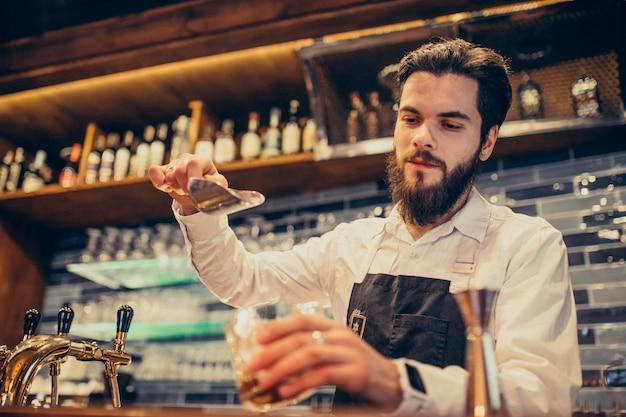 Barista bello che fa bere e cocktail ad un contatore