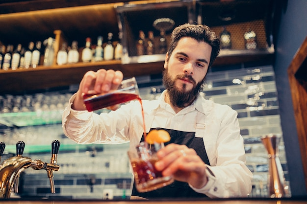 Handsome bartender making drinking and cocktails at a counter