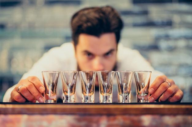 カウンターで飲むとカクテルを作るハンサムなバーテンダー男