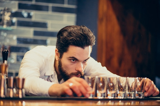Handsome bartender man making drinking and cocktails at a counter