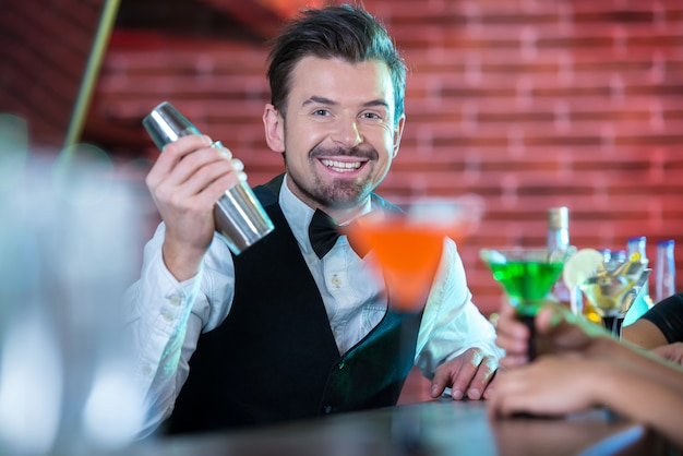 Handsome bartender serving cocktail to attractive woman.