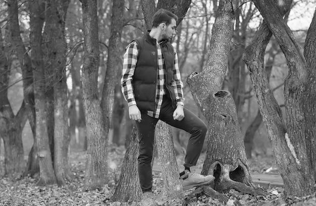 Красивый мужчина с бородой в осеннем парке позирует на камеру