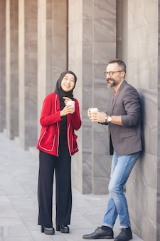 Handsome beard middle aged businessman drinking coffee at outdoor coffee cafe with young beautiful muslim woman