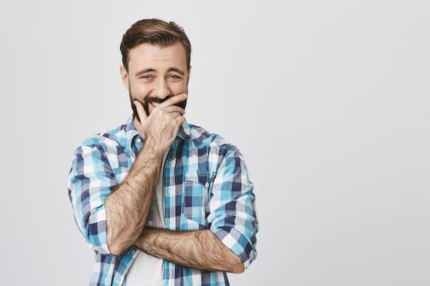 Красивый бородатый взрослый мужчина смеется, прикрывая рот