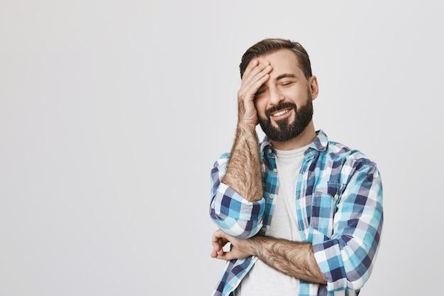 Красивый бородатый взрослый мужчина смеется над шуткой