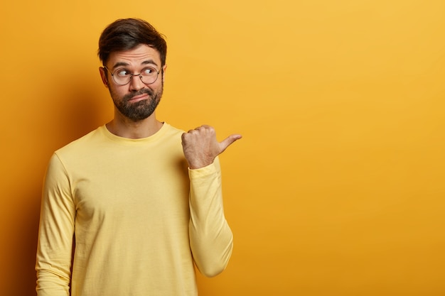 Handsome bearded adult man points thumb aside, shows banner or advertisement, tells to visit online store, dressed casually, isolated on yellow wall, found what he need. monochrome shot.