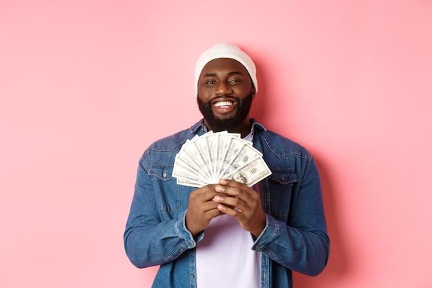 Bell'uomo afroamericano barbuto che mostra soldi, guadagna dollari, in piedi su sfondo rosa