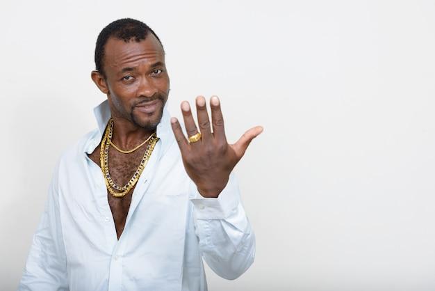 Красивый бородатый африканец в образе гангстера у белой стены