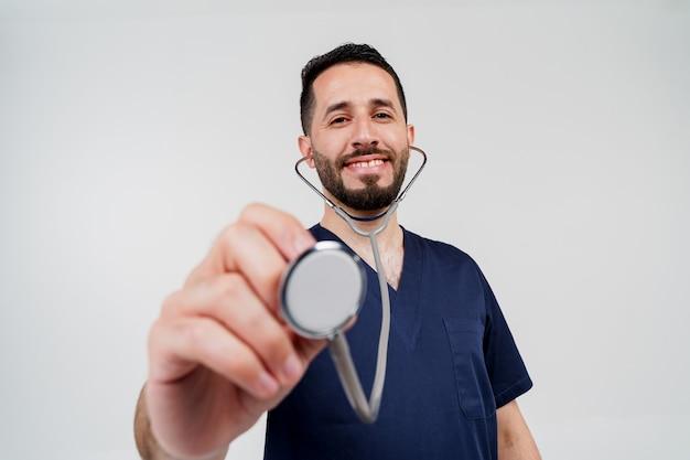 ホーン内視鏡を持つハンサムなひげを生やしたアラブの医師は、患者に聴診を行います。
