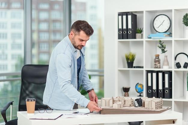 Красивый бородатый архитектор работает над строительным проектом, он рассматривает модель, над которой работает