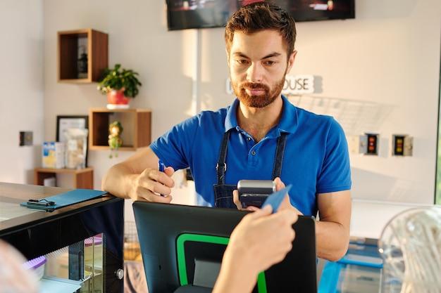 Красивый бородатый бариста дает кредитную карту клиенту, оплачивающему еду с помощью кредитной машины