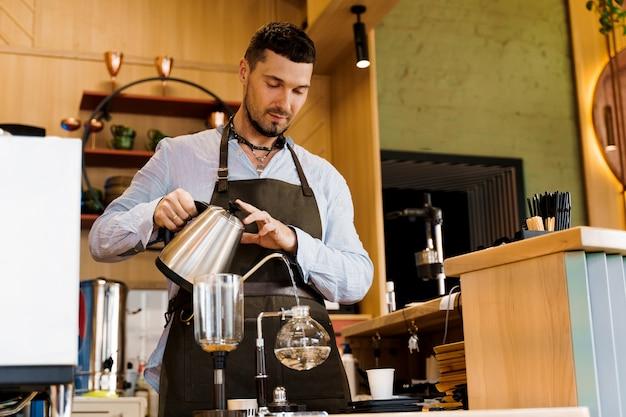 ハンサムなひげを生やしたバリスタは、カフェでコーヒーを淹れるために、カトルからサイフォン装置に熱湯を注ぎます
