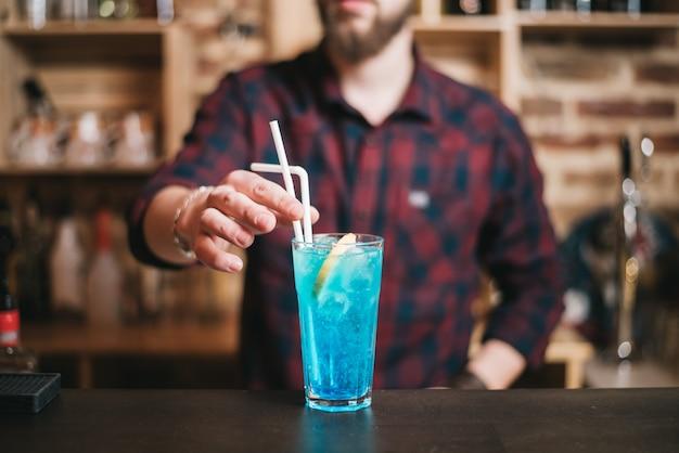 Красивый бородатый бармен готовит коктейль