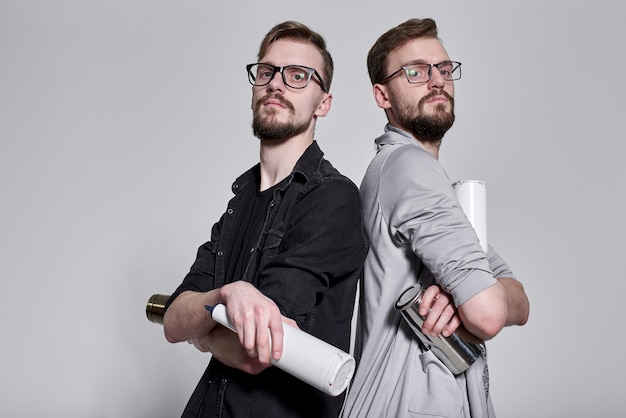 Handsome bearded bartenders twins juggling with shaker and bottles on gray wall