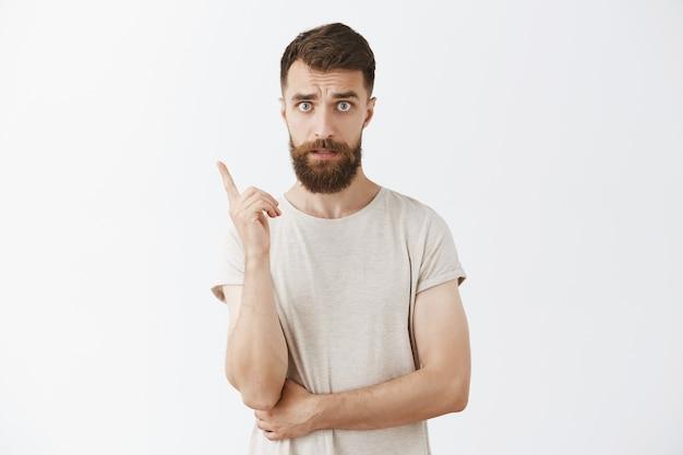 Uomo barbuto barbuto bello che posa contro il muro bianco