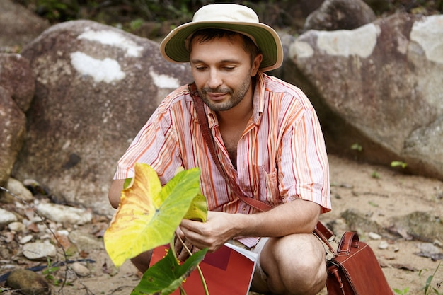 Handsome bearded biologist wearing hat holding leaf of green plant, looking with friendly and caring expression during his environmental studies at work field.