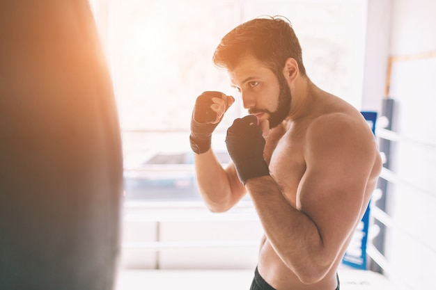 Handsome bearded boxer with bare torso is practicing punches at the fight club