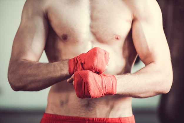 Handsome bearded boxer with bare torso wrapping his hands.