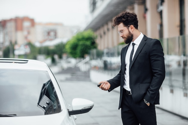 Handsome bearded businessman in black suit entering his car while standing outdoors on the streets of the city near the modern office center