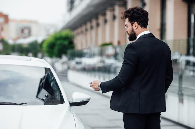 검은 양복을 입은 잘생긴 사업가가 현대적인 사무실 센터 근처 도시 거리에 야외에 서 있는 동안 차에 들어갔다