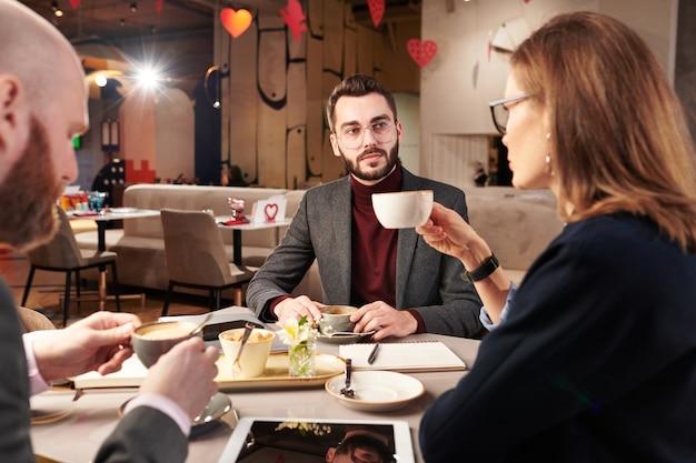 Красивый бородатый бизнесмен в очках пьет кофе с деловыми партнерами при обсуждении плана сотрудничества