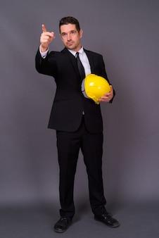 Красивый бородатый бизнесмен в костюме инженера в каске у серой стены