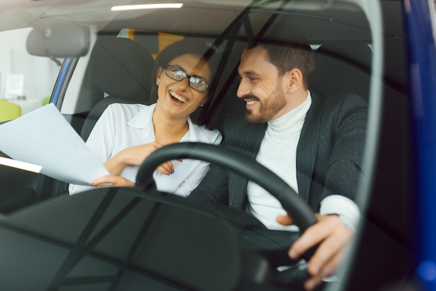 ハンサムなひげを生やした実業家は車のディーラーで新しい車に座っています。