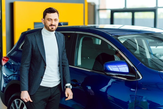 Handsome bearded buyer in casual wear in dealership, guy looks on camera while standing near car with crosed arms