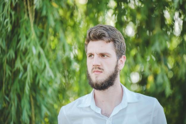 Bell'uomo caucasico barbuto con una polo bianca