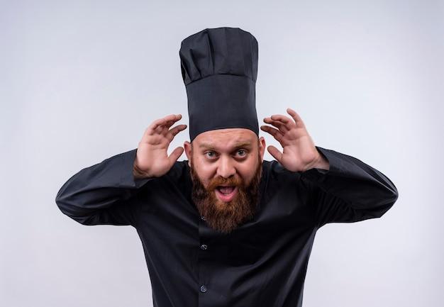 Un uomo bello chef barbuto in uniforme nera che tiene le mani sulle orecchie cercando di sentire qualcosa su un muro bianco