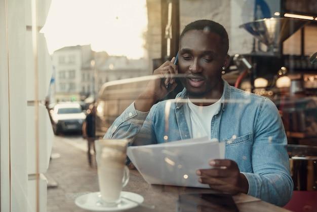 Красивый бородатый темнокожий бизнесмен сидит возле окна кафе и разговаривает по смартфону с
