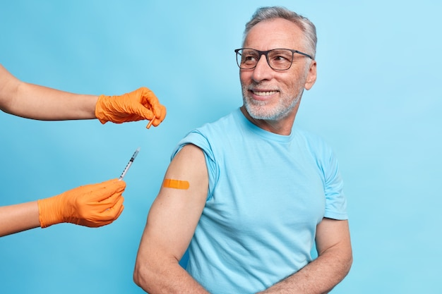 Handsome bearded elderly man gets coronavirus vaccination shows arm with adhesive tape looks attentively at doctor