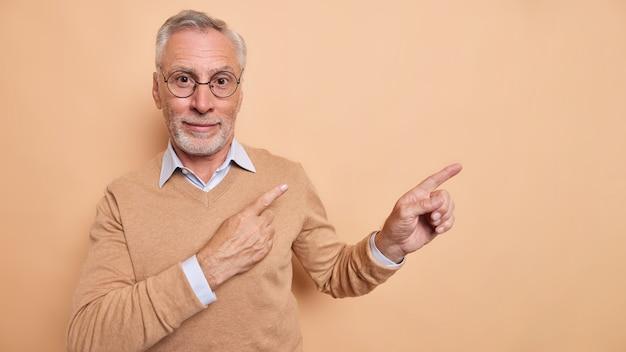 ハンサムなひげを生やした老人が空白のコピースペースを指差す