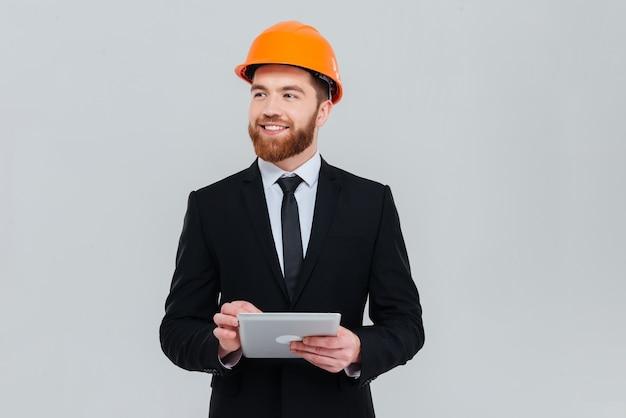 수염을 기른 잘생긴 엔지니어는 양복과 헬멧을 쓰고 태블릿 컴퓨터를 옆으로 바라보고 있습니다. 격리 된 회색 배경