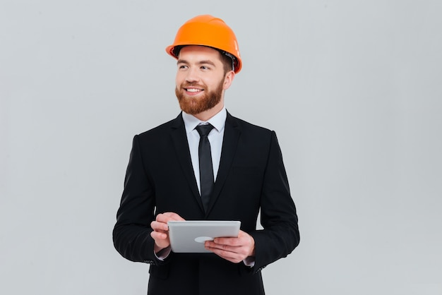 Handsome bearded engineer in suit and helmet with tablet computer looking aside. isolated gray background
