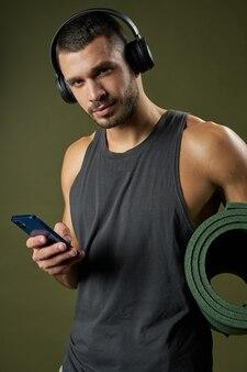 녹색 배경에 격리된 손에 피트니스 매트가 있는 헤드폰을 끼고 수염을 기른 잘 생긴 피트니스 트레이너