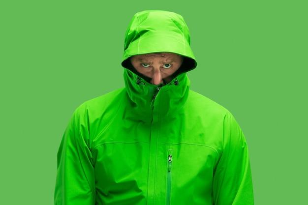Bel barbuto congelamento giovane uomo isolato su vivido colore verde alla moda in studio. concetto dell'inizio dell'autunno e del freddo