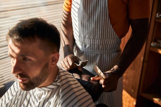 理髪店で散髪をしているハンサムなひげを生やした紳士