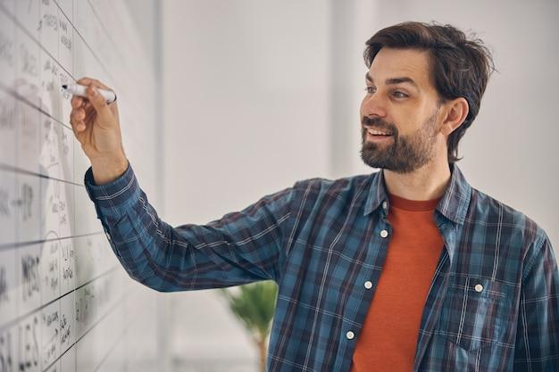 プロジェクト戦略と笑顔に取り組んでいる市松模様のシャツのハンサムなひげを生やした紳士