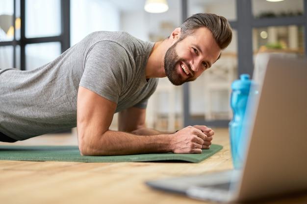 ノートパソコンでオンライントレーニングを見て、運動しながら笑顔のハンサムなひげを生やした紳士
