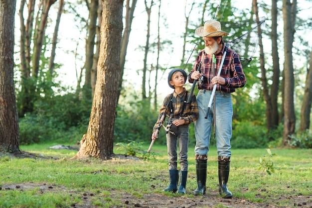 Красивый бородатый дедушка проводит досуг с внуком на рыбалке. концепция времени семьи и хобби.