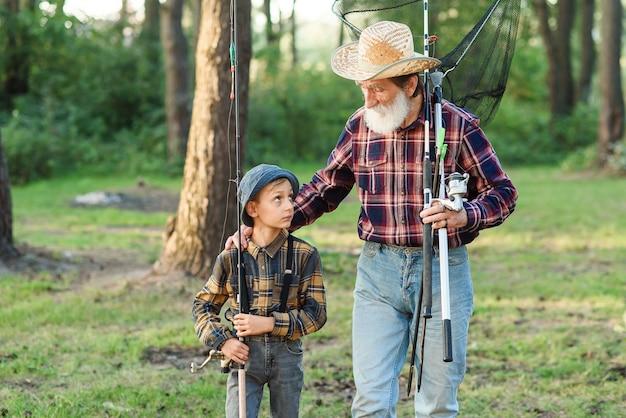낚시가는 그의 손자와 함께 여가를 보내는 잘 생긴 수염 난된 할아버지. 가족과 취미 시간