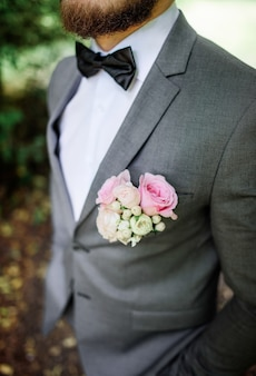 Handsome bearded groom in grey suit with pink boutonniere poses in the park