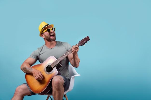 노란색 모자와 선글라스에 잘 생긴 수염 기타리스트는 의자에 앉아 파란색에 고립 된 어쿠스틱 기타를 연주하는 동안 노래
