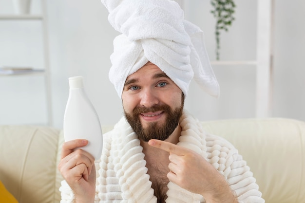 Handsome bearded guy applying moisturizer body cream from container. spa, body and skin care for man concept. place for advertisement