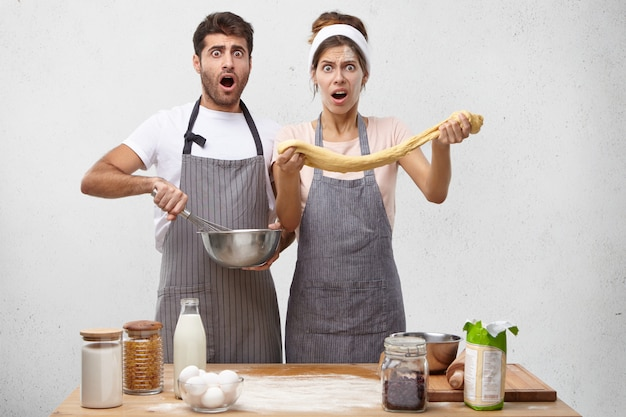 Handsome bearded guy and cute woman feeling shocked and terrified looking like a mess while baking pastry